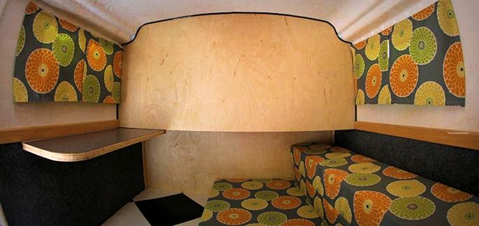 Hjemmekoselig idyll om enn litt spartansk. Vegghylla til venstre er ekstrautstyr. Sofa om dagen og seng om natten. Mulighet for å koble til TV og internett.